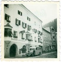 Gasthof Ledererbräu (heute Lederer Brauhaus) mit Bushaltestelle in der Bienerstraße 84 in Rattenberg, Tirol, Gelatinesilberabzug 6 x 6 cm ohne Impressum (Amateuraufnahme) 1952.  Inv.-Nr. vu606gs00005