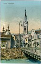 Nepomuk-Adler-Brücke über den Eisack und Pfarrkirche St. Michael mit dem Weißen Turm in Brixen am Eisack. Photochromdruck 9 x 14 cm; Impressum: Verlag Jos(ef). Bergmeister, Papierhandlung, Brixen um 1910.  Inv.-Nr. vu914pcd00207