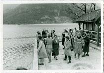 """Reisegruppe auf der Uferterrasse  des Hotel """"Molveno"""" am gleichnamigen  See im Trentino.  Gelatinesilberabzug 10 x 15 cm;  Privataufnahme, Ausarbeitung von  Foto Skulina, Torbole am Gardasee 1957.  Inv.-Nr. vu105gs00101"""