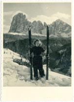 Skiläuferin vor der Bergkulisse der Langkofelgruppe in den Südtiroler Dolomiten nach dem Abschnallen der Skier. Gelatinesilberabzug 10 x 15 cm; ohne Impressum, um 1940.  Inv.-Nr. vu105gs00008