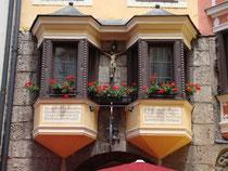 Haussegen mit Kruzifix an den Erkern vom zweiachsigen, fünfgeschoßigen Bürgerhaus Herzog-Friedrich-Straße 9 in der Altstadt von Innsbruck. Digitalphoto; © Johann G. Mairhofer 2012.  Inv.-Nr.  1DSC03480