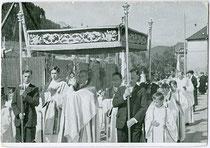 Erste Fronleichnamsprozession der Notkirche Wilten-West, Innsbruck im Jahr 1936; Geistlicher unter dem Baldachin trägt die Monstranz nach Verhüllen seiner Hände mit dem Velum. Autotypie 10 x 15 cm ohne Impressum.  Inv.-Nr. vu105at00005