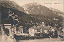 Mühlau mit Kettenbrücke (1843-1938) und rechts Eisenfachwerkbrücke (1891-1939) der Localbahn Innsbruck-Hall in Tirol (L.B.H.i.T.) über den Inn gegen die Nordkette. Lichtdruck 9 x 14 cm; Impressum: Ottmar Zieher, München um 1910.  Inv.-Nr. vu914ld00335