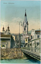 Adlerbrücke über den Eisack, Adlerbrückengasse und Pfarrkirche St. Michael mit dem Weißen Turm in Brixen am Eisack. Photochromdruck 9 x 14 cm; Impressum: Verlag Jos(ef). Bergmeister, Papierhandlung, Brixen um 1910.  Inv.-Nr. vu914pcd00207