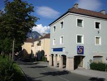 """Mehrfamilienwohnhaus Kärntner Straße 60 der Optionszeit (1940 – 1943) mit Café """"Socke"""" in Innsbruck-Reichenau, ein Laubenhaus mit an der Nordfassade hindurchführendem Gehsteig. Digitalphoto; © Johann G. Mairhofer 2011.  Inv.-Nr. 1DSC01678"""