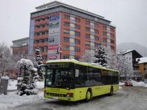 Postbus des Regioverbunds am Bahnhofvorplatz in Wörgl, Bezirk Kufstein, Tirol mit Hochhaus Bahnhofstraße 53. Digitalphoto; © Johann G. Mairhofer 2010.  Inv.-Nr. DSC01252