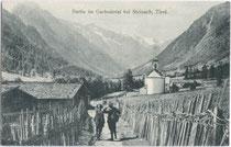 Bergwanderer auf einer mit Flechtzaun gesäumten Talstraße in Gschnitz, Bezirk Innsbruck-Land, Tirol. Lichtdruck 9 x 14 cm; Impressum: K(arl). Redlich, Innsbruck um 1910.  Inv.-Nr. vu914ld00030