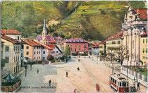 Franz-Joseph-Platz (heute: Grieser Platz) in Gries mit Haltestelle der Grieser Linie der Bozner Straßenbahn (1909 bis 1948). Farbautotypie 9 x 14 cm; Impressum: Sormani, Milano um 1925.  Inv.-Nr. vu914fat00022