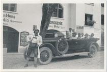 Chauffeur - evtl. zugleich der Mietwagenunternehmer - im Automantel bei einer Ausfahrt mit Sommerfrischlern in Mayrhofen im Zillertal, Bzk. Schwaz, Tirol. Gelatinesilberabzug 6 x 9 cm, wohl Amateuraufnahme um 1930.  Inv.-Nr. vu609gs00034