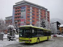 Postbus des Regioverbunds am Bahnhofvorplatz in Wörgl, Bezirk Kufstein, Tirol mit Hochhaus Bahnhofstraße 53. Digitalphoto; © Johann G. Mairhofer 2010.  Inv.-Nr. 1DSC01252
