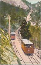 Die Wägen der 1903 eröffneten Mendelbahn von St. Anton, Marktgemeinde Kaltern, ehem. Bzk. Bozen auf die Mendel mit den Luftkurhotels beim Passieren der Ausweiche. Photochromdruck 9 x 14 cm; Impressum: Johann F. Amonn, Bozen 1907.  Inv.-Nr. vu914pcd00365