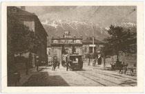 Halt eines Triebwagens mit zwei Beiwagen der Haller Linie vor Durchfahrung der Triumphpforte in Innsbruck-Wilten. Rastertiefdruck 9 x 14 cm ohne Impressum, um 1920.  Inv.-Nr. vu914rtd00002