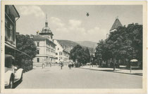 Rathaus mit Postamt und Sparkasse (von vorne nach hinten) in Bruneck an der am Graben entlang verlaufenden Pustertaler Staatsstraße. Lichtdruck 9 x 14 cm; Impressum: Editore Joh(ann). Amonn, Bolzano 1936.  Inv.-Nr. vu914ld00269