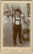 Knabe im Lernalter mit Wanderstock und Hündchen. Albuminabzug auf Untersatzkarton 10,5 x 6, 5 cm (Visitformat); Impressum: Michael Lackner, Maler und Photograph, Kirchberg (in Tirol) um 1890.  Inv.-Nr. vuVIS-00231