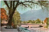 Meraner Kurpromenade zwischen Reichsbrücke (heute Postbrücke, rechts im Bild) von 1909 und der Theaterbrücke. Photochromdruck 9 x 14 cm; ohne Impressum um 1910.  Inv.-Nr. vu914fat00081
