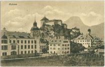 """Bezirksgericht (li.) und Gasthof """"Buchauer"""" (Bildmitte) in Kufstein gegen den Pendling. Lichtdruck 9 x 14 cm; Impressum: D(avid). Amort, Kufstein um 1907.  Inv.-Nr. vu914ld00288"""