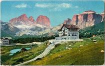 """Hotel """"Pordoi"""" (2.140 m) an der Dolomitenstraße in Canazei im Fassatal (1868-1919 Bzk. Cavalese, Gef. Grafsch. Tirol) mit Langkofel (3.178 m) und Sella (3.152 m). Photochromdruck 9 x 14 cm; Impressum: Joh. F. Amonn, Bozen 1909.  Inv.-Nr. vu914pcd00265"""