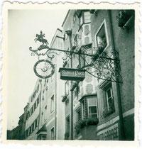 """Schmiedeeisernes und vergoldetes Wirtsschild vom Gasthof """"zur Post"""" in der Südtiroler Straße in Rattenberg, Tirol. Gelatinesilberabzug 6 x 6 cm (Amateuraufnahme) 1952.  Inv.-Nr. vu606gs00003"""