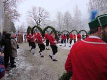 5815 - Der Tanzmeister hebt seinen bebänderten Stock und der Vortänzer beginnt mit dem typischen Schritt des Schäfflertanzes einen Kreis zu tanzen. Die übrigen Tänzer, verbunden durch die Bogengirlande, folgen ihm.