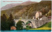 """Steinbogenbrücke der Fernpassstraße über den Fernsteinsee, Gasthof """"Schloss Fernsteinsee"""" mit Bootshaus und die Ruine der ehem. Zollburg Fernstein (v.v.n.h.). Photochromdruck 9 x 14 cm; Impressum: Edition Photoglob, Zürich um 1910.  Inv.-Nr. vu914pcd00180"""