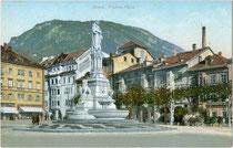 """Watherplatz in Bozen mit Denkmal für Walther von der Vogelweide und Hotel """"Schgraffer"""". Photochromdruck 9 x 14 cm; Impressum: Joh(ann). F(ilibert). Amonn, Bozen um 1910.  Inv.-Nr. vu914pcd00213"""