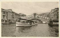 Vaporetto (Wasserbus) der ACTV (Azienda del consorzio trasporti veneziano) auf dem Canal Grande und die San Marco und San Polo verbindende Rialto-Brücke. Autotypie 9 x 14 cm; Impressum: Ed. C. Capello, Milano-Venezia um 1930.  Inv.-Nr. vu914at00035