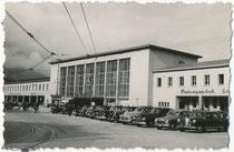 Personenkraftwagen vor dem 2. Hauptbahnhof am Südtiroler Platz in Innsbruck im Eröffnungsjahr 1956 (für den heutigen Gebäudekomplex 2004 geschleift worden). Gelatinesilberabzug ca. 5 x 7,5 cm ohne Impressum (Amateuraufnahme).  Inv.-Nr. vu609gs00035