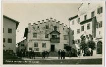Plunerschneider-Haus (in Bildmitte) und der seit 1919 als Rathaus genutzte ehem. Ansitz Krausegg (rechts) am Marktplatz von Kastelruth. Gelatinesilberabzug 9 x 14 cm; Impressum: Foto Misinato, Seis am Schern um 1935.  Inv.-Nr. vu914gs00327