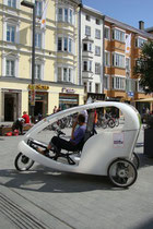 Mit elektrischer Anfahrhilfe ausgestattete, moderne chinesische Fahrradrikscha für Lenker und zwei Passagiere oder Ladegut am Nordende der Maria-Theresien-Straße in Innsbruck. Digitalphoto; © Johann G. Mairhofer 2014.  Inv.-Nr. 2DSC00996