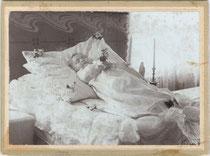 Aufbahrungsbild eines Kleinkindes. Gelatinesilberabzug auf Untersatzkarton 10,8 x 16,6 cm (Cabinetformat). Impressum: Hermann Schwaiger, Landeck um 1895.  Inv.-Nr. vuCAB-00259