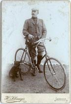 Junger Mann mit Rennsportrad in Norfolk-Jacket und Knickerbockers.  Gelatinesilberabzug auf Untersatzkarton  16,6 x 10,8 cm. Impressum:  H(einrich). Schwaiger, Landeck in Tirol  (vormals in Sterzing) um 1900. Inv.-Nr. vuCAB-00050