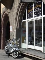 """Mit milieutypischen Stickern dekorierter Motorroller im Stil der """"Mods"""", abgestellt vor einem Plattenladen in der Universitätsstraße in Innsbruck (mittlerweile übersiedelt). Digitalphoto; © Johann G. Mairhofer 2012.  Inv.-Nr.  1DSC02835"""
