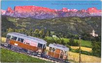 Wagengarnitur der Rittnerbahn vor dem Schlernmassiv unterwegs auf der Zahnradstrecke talwärts nach Bozen. Photochromdruck 9 x 14 cm; Impressum: Lorenz Fränzl Bozen, um 1910.  Inv.-Nr. vu914pcd00119