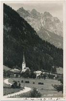 St. Jakob in Haus an der Pillerseetal Landesstraße (L2), Bzk. Kitzbühel, Tirol mit Pfarrkirche gegen Loferer und Leoganger Steinberge (AVE 9). Gelatinesilberabzug 9 x 14 cm; Impressum: Ad(olf). Künz, Anichstr. 32, Innsbruck um 1930.  Inv.-Nr. vu914gs01213