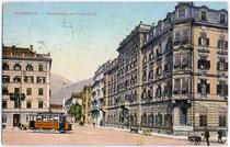 """Straßenbahntriebwagen Tw 43 am Bahnhofplatz (heute Südtiroler Platz) mit Hotels """"de l'Europe"""" (li.) und """"Tyrol"""" (re.). Photochromdruck 9 x 14 cm; Impressum: K(arl). Redlich, Innsbruck.  Inv.-Nr. vu914pcd00104"""