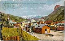 Bahnhofsareal der ehemaligen Grödnerbahn (1915/16-1960) in St. Ulrich in Gröden/Urtijei, ehem. Gerichtsbezirk Kastelruth, Bzk. Bozen (heute Bezirksgemeinschaft Salten-Schlern). Farbautotypie 9 x 14 cm um 1920, ohne Impressum.  Inv.-Nr. vu914fat00048