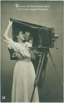 Spruchkarte mit amouröser Szene unter schwarzem Einstelltuch für die Abschattung der Mattscheibe zur Aufnahmeeinstellung einer großformatigen Balgenkamera. Gelatinesilberabzug 9 x 14 cm eines nicht firmierenden Verlags um 1910.  Inv.-Nr. vu914gs01106