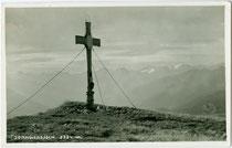Gipfelkreuz auf dem Vorderen Sonnwendjoch (2.224 m.ü.A.), dem südöstlichen Ausläufer des Rofangebirges mit Blick gegen Süden in das Zillertal. Gelatinesilberabzug 9 x 14 cm; Impressum: Ad. Künz, Anichstr. 32, Innsbruck um 1935.  Inv.-Nr. vu914gs00795