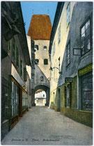Kreuzgasse mit Bräuhaustor (Säbener Tor) in der Altstadt von Brixen. Photochromdruck 9x14cm; Joh(ann). F(ilibert). Amonn, Bozen um 1907.  Inv.-Nr. vu914pcd00084