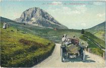 Tonneau der Marke Métallurgique unterwegs auf der Dolomitenstraße nach Canazei im Fassatal gegen Piz Boè (3.152m s.l.m.) und Pordoijoch in der Sellagruppe der Dolomiten. Photochromdruck. 9 x 14 cm; Joh. F. Amonn, Bozen 1909.  Inv.-Nr. vu914pcd00377