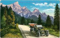Automobil mit Chauffeur auf der Rollepassstraße vor der Palagruppe mit Cimon della Pala (3.184m) in den Dolomiten. Photochromdruck 9x14cm; Impressum: Joh(ann). F(ilibert). Amonn, Bozen um 1910.  Inv.-Nr. vu914pcd00211