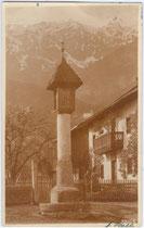Säulenbildstock mit schindelgedecktem Zeltdach, errichtet um 1600 am Dorfplatz in Thaur, Bzk. Innsbruck-Land, Tirol. Gelatinesilberabzug 9 x 14 cm;  Impressum: A(ugust). Riepenhausen, Hall in Tirol, postalisch befördert 1916.  Inv.-Nr.  vu914gs00057