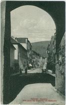 Stadtgasse in Bruneck vom Klostertor beim Ursulinenkloster aus. Lichtdruck 9 x 14 cm; Impressum: Stengel & Co. G.m.b.H., Dresden 1909.  Inv.-Nr. vu914ld00271