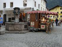 Ambulanter Marktstand eines Viktualienhändlers beim Stadtbrunnen in der Hinterstadt, gestaltet von akad. Bildhauer Sepp Dangl (1927-1993) zum 700. Stadtjubiläum von Kitzbühel. Digitalphoto; © Johann G. Mairhofer 2015.  Inv.-Nr. 2DSC03210
