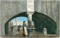 Wasserträgerin in Torbole, Alto Garda e Ledro, Trentino beim Brunnen unter dem Goethedenkmal. Photochromdruck 9 x 14 cm; Impressum: Joh(ann). F(ilibert). Amonn, Bozen um 1907.  Inv.-Nr. vu914pcd00110