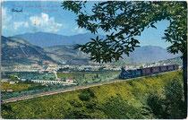 Personenzug der Ferrovia della Valsugana (heute: Ferrovia Trento-Venezia) auf einem über Normalhöhe hinaus gehenden Dammbau vor dem Viadotto Gocciadoro (li.) in Trient. Photochromdruck 9 x 14 cm; Impressum: Joh(ann). F(ilibert). Amonn, Bozen 1907.  Inv.-N