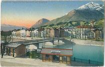 """Haltestelle """"Innbrücke"""" der Linie 2 in der Herzog-Otto-Straße mit Pissoir (Mitte) und Abort (links). Photochromdruck 9 x 14 cm; Impressum: Wilhelm Stempfle, Innsbruck um 1910.  Inv.-Nr. vu914pcd00214"""