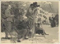 Filmstab bei nicht bezeichneten Dreharbeiten in winterlicher Berglandschaft. Gelatinesilberabzug 9 x 12 cm ohne Impressum (wohl Amateuraufnahme).  Inv.-Nr. vu912gs00019