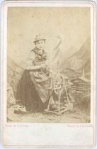Junge Frau in ländlicher Kleidung am Spinnrad vor gemalter Hintergrundkulisse des Photoateliers. Albuminabzug auf Untersatzkarton 16,5 x 10,5 cm (Cabinet-Format); Impressum: C(arl). A(lexander). Czichna, Innsbruck um 1870.  Inv.-Nr. vuCAB-00040