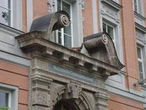 Portalaufsatz mit Voluten im Mittelrisalit vom Akademischen Gymnasium in Innsbruck, Angerzellgasse 14 (errichtet 1909/10). Digitalphoto, © Johann G. Mairhofer 2012.  Inv.-Nr. 1DSC04253